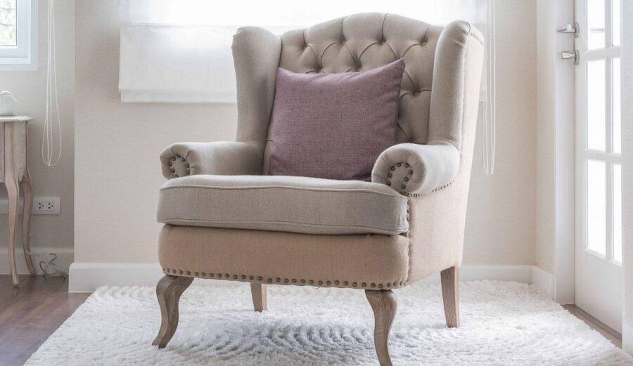 sillón orejero beige con almohadones de conforama